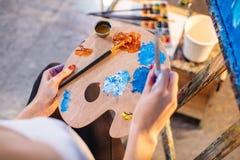 Mischende Ölfarben der Künstlerin auf der Palette, die in ihrer Hand hält Lizenzfreies Stockbild