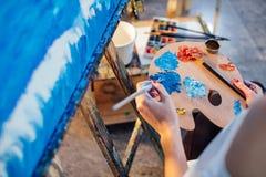 Mischende Ölfarben der Künstlerin auf der Palette, die in ihrer Hand hält Stockfotografie
