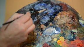 Mischende Farben des Künstlers auf einer Palette stock footage