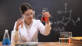 Mischende Flüssigkeiten des Chemiestudenten im Labor und in den schreiben Ergebnissen, Experiment stock footage