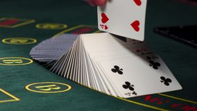 Mischende Karten des Croupiers, Shows eine auf grüner Tabelle am Kasino stock video