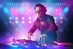 Mischende Musik des Diskjockeys auf Drehscheiben auf Stadium mit Lichtern und Stockfotos