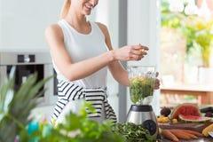 Mischendes Gemüse der glücklichen Frau des strengen Vegetariers stockbilder