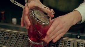 Mischendes Rot des Kellners spritz Aperitif aperol Cocktail mit Eiswürfeln und -gießen es in ein leeres Glas stock video