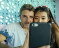 Mischethniepaare beim Liebeslächeln nett mit hübschem kaukasischem Mann und der schönen asiatischen japanischen Frau, die Hand stockbild
