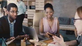 Mischethnieteambesprechung im modischen Büro Glückliche lächelnde kreative millennials lösen gedanklich und entwickeln Geschäft 4 stock footage