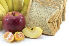 Mischfrüchte und Brot auf weißem Hintergrund Lizenzfreie Stockfotos