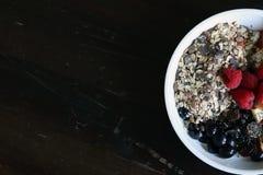 Mischfrucht und Getreide in einer weißen Schüssel auf braunem Holztisch Lizenzfreies Stockfoto