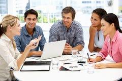 Mischgruppe um Tabelle im Geschäftstreffen Stockfotos