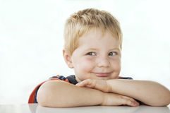 Mischief. Young boy with blonde hair and green eyes has an ornery grin, and his eyes diverted for a look of mischief Royalty Free Stock Photos