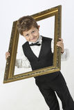 Mischievious boy looks through picture frame Royalty Free Stock Images