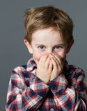 Mischievous beautiful child with excited blue eyes for shyness. Mischievous beautiful young 6-year old child with excited blue eyes enjoying hiding his smiling Stock Photos