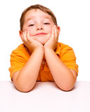 Mischievous and bored child sitting at desk Royalty Free Stock Photo