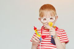 Mischievous boy playing doctor. Toy syringe, glasses and phonend. Oscope. Portrait Stock Photography