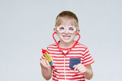 Mischievous boy playing doctor. Toy syringe, glasses and phonend. Oscope. Portrait Stock Images