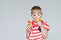 Mischievous boy playing doctor. Toy syringe, glasses and phonend. Oscope. Portrait Stock Image