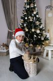Mischievous boy is taking out the brown teddy bear from the bask. Mischievous boy in white sweater and Santa red hat is sitting near decorated Christmas tree and Stock Photography