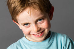 Mischievous child with freckles and adorable blue eyes smiling Royalty Free Stock Images