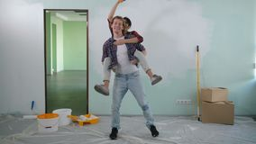 Mischievous couple renovating house interior. Mischievous multiracial couple renovating their new house interior, dancing happily and carefreely indoors. Joyful stock footage