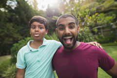 Mischievous father and son enjoying at park. Portrait of mischievous father and son enjoying at park Royalty Free Stock Photos