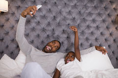 Mischievous father and son taking selfie on bed Stock Photography