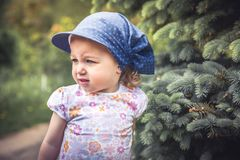 Mischievous frouned child girl portrait among fir trees on blurred background. Mischievous frouned cute child girl portrait among fir trees on blurred background Stock Photos