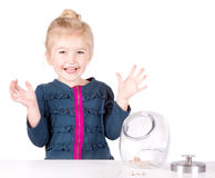 Mischievous girl steals cookies from cookie jar. Isolated on white background Royalty Free Stock Photo