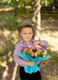 Mischievous little boy with flowers Royalty Free Stock Image