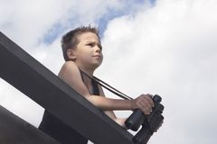 The mischievous little boy holds the binoculars in his hands and peers into the distance Royalty Free Stock Photos