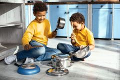 Mischievous little boys creating cacophony by drumming on saucepans. Little musicians. Cheerful little boys creating cacophony by drumming on saucepans in the Stock Photo