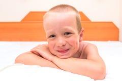 Mischievous preschooler resting in bed Stock Photo