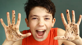 Mischievous teen boy with dirty hand smile Stock Photo