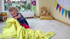 Mischievous toddler girl hide under yellow plaid blanket on floor stock video footage