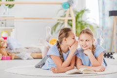 Mischievous twin sisters whispering secrets. Lying on a white rug in a cozy children`s bedroom Royalty Free Stock Images