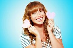 Mischievous valentine girl holding two love hearts Royalty Free Stock Images