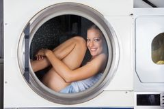 Mischievous Woman Sitting Inside Washing Machine Royalty Free Stock Photography