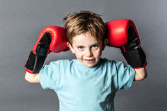 Mischievous young boy with freckles holding his boxing gloves up Royalty Free Stock Images