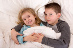 Mischievous young brother and sister in bed. Grinning up at the camera as they lie side by side under the duvet preparing to go to sleep Royalty Free Stock Images