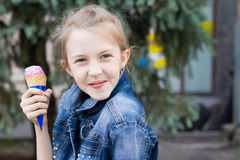 Mischievous young girl enjoying an ice cream cone Royalty Free Stock Photography