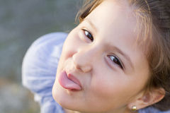 Mischievous young girl sticking out her tongue Stock Photography