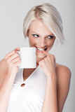 Mischievous young woman drinking coffee Royalty Free Stock Photo