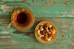 Mischnüsse auf einer gelbes Metalluntertasse und einer Glasschale türkischem Tee auf einem hölzernen Hintergrund des Türkises Stockfoto