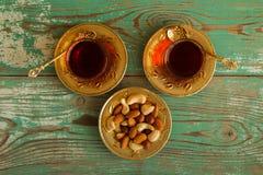 Mischnüsse auf einer Metalluntertasse und zwei Glasschalen türkischem Tee auf einem hölzernen Hintergrund des Türkises, Draufsich Lizenzfreies Stockfoto