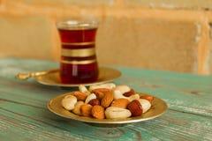 Mischnüsse auf einer Untertasse und einer Glasschale türkischem Tee auf einem Türkisholztisch auf dem Hintergrund einer Backstein Lizenzfreies Stockfoto