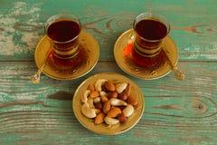 Mischnüsse auf einer Untertasse und zwei Glasschalen türkischem Tee auf einem hölzernen Hintergrund des Türkises Stockfoto