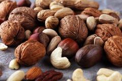 Mischnüsse auf grauem Hintergrund Gesundes Lebensmittel und Snack Walnuss, p Lizenzfreies Stockfoto
