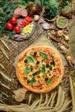 Mischpizza mit Huhn, Pfeffer, Oliven, Zwiebel, Basilikum auf Pizzabrett lizenzfreie stockfotos