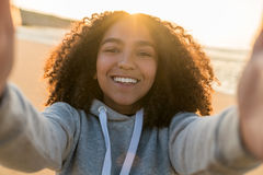 Mischrasse-Afroamerikaner-Mädchen-Jugendlicher, der Selfie auf Strand nimmt Stockfotografie