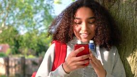 Mischrasse-Afroamerikanermädchenjugendlicher, der an einem Baum unter Verwendung des Handys sich lehnt stock video