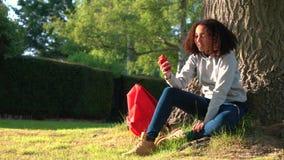 Mischrasse-Afroamerikanermädchenjugendlicher, der Telefon durch einen Baum verwendet stock video